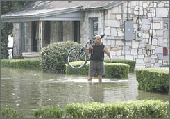 Joe Mezzina removes a bike from his flooded bike shop in Tallahassee. Rain from Tropical Storm Fay caused his shop to flood when a nearby lake overflowed.