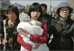 Zeng Jinyan, center, wife of jailed Chinese civil activist Hu Jia, carries her baby and walks with mother-in-law Feng Juan, right, in April.