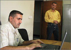 Maj. Ahmed Khathem, left, head of Iraq's cybercrimes division, and Lt. Alaa Hussein of an anti-hacker team set up the unit's lone computer, a laptop borrowed from one of the unit's officers.