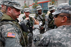 Louisiana National Guard Sgt. 1st class Anthony Stuttle, right, instructs members of the 256th Charlie Co. to secure their vehicles before moving into the Ernest N. Morial Convention Center in New Orleans.