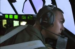 Lt. Mike Anderson, a co-pilot on a C-130 scans the outside of the Hurricane Hunter, Friday while flying a mission in the Caribbean Sea and into Hurricane Gustav.