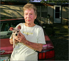 Ada Noda, 80, poses for a picture with her puppy Lolita in front of her home in Saint Augustine, Fla. Suffocating in debt, the 80-year-old did something she never thought she'd be forced to do. She declared bankruptcy.