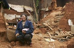 Li Fucui, 47, cries in front of the debris of her collapsed house, which buried her brother-in-law, after an earthquake hit Lixi town of Huili County, Sichuan province