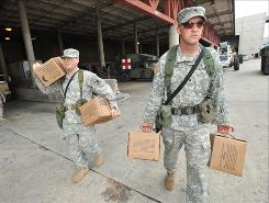 Spc. Sean Davis, right, and Sgt. Michael Hartman both from the Louisiana Army National Guard load up MREs on Sunday as they prepare to patrol from their temporary base at the Morial Convention Center in New Orleans.