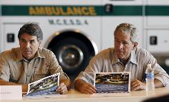 President Bush, right, and Texas Gov. Rick Perry, left, are briefed during a visit Monday to the Alamo Regional Command Center at Lackland Air Force Base, in San Antonio, Texas.