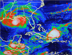 A National Hurricane Center video monitor displays an infrared satellite view of both Hurricane Gustav, left, and Tropical Storm Hanna, right, on Monday at the hurricane center in Miami.