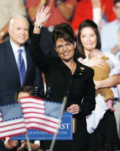 Alaska Gov. Sarah Palin, foreground, waves during a campaign rally Friday in Dayton, Ohio. Her daughter, Bristol (holding the governor's son, Trig), is to the right, in the background.