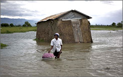 A woman stands near a mud thatch home during flooding from Tropical Storm Hanna in L'Artibonite, northern Haiti, Tuesday.