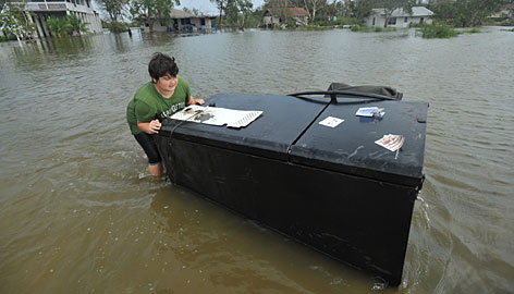 Kimothy Guy, 14, floats a refrigerator while helping his neighbor clean belongings out of a flooded home.