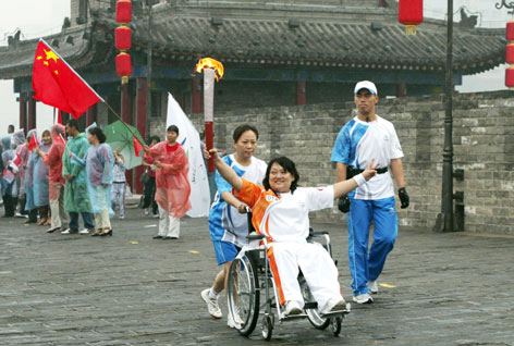 A Chinese torchbearer for the 2008 Beijing Paralympic Games celebrates in Xian on Aug. 30. The Paralympic relay involves 850 torchbearers and showcases ancient and modern China.