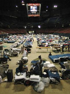 Hundreds of New Orleans area evacuees fill the floor of the Birmingham-Jefferson Convention Complex on Thursday in Birmingham, Ala. The federal government says it will reimburse the hotel expenses of some of the nearly 2 million evacuees, but the news that hotel costs might be reimbursed was too late for people who have been spending nights at public shelters.