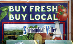 A sign advocating buying fresh and local in the Shenandoah Valley is tacked on a bulletin board at the Shenandoah Valley Produce auction in Dayton, Va. Amish, Mennonite and non-religious small-scale growers are trying to adapt to the country's expanding diet for locally grown foods.