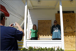 Tourists pose for a picture Sunday in Key West, Fla., in front of a shop boarded up in anticipation of Hurricane Ike.