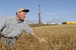 Doug Kinnoin inspects one of his canola fields near Stanley, N.D. An oil well stands on his property behind him.
