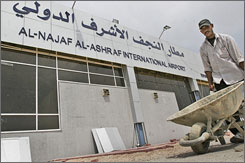 A construction worker wheels bricks at an airport under construction in Najaf, Iraq, on Aug. 25.