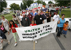 Hundreds of people march in Potsville, Iowa, during an immigration rally after a federal raid of the local Agriprocessors plant in May.