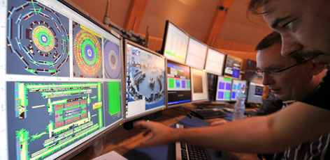 European Center for Nuclear Research (CERN) scientists control computer screens showing traces on Atlas experiment of the first protons injected in the Large Hadron Collider during its switch on operation at the Cern's press center on Wednesday.