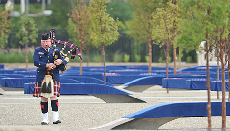 A bagpiper plays as he strolls amid 184 steel-and-granite benches at the Pentagon Memorial representing those who died when Flight 77 struck the building.
