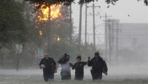 A police officer, right, helps residents evacuate as a house burns in the background as Hurricane Ike barrels toward Galveston, Texas, on Friday.