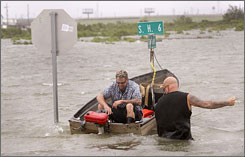 Bob Spillers, right, helps neighbor Jack Horne start a boat so he can return to his home flooded by the tidal surge ahead of Hurricane Ike in Hitchcock, Texas, on Friday.