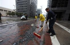 Jim Boyles, in blue, and Mark Wilson, in yellow, sweep up glass at the 600 block of Travis Street. Much of the glass came from the J .P. Morgan Tower.