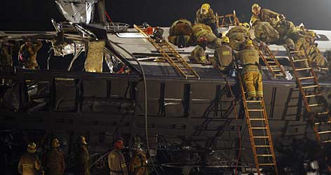 Firefighters work into the night to rescue trapped passengers at the site of a train crash.