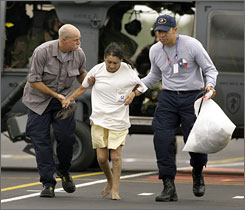 Aurora Krichick, 55, is escorted from a military helicopter at Texas City High School after being rescued from Port Bolivar, Texas, where she says Hurricane Ike destroyed her home Saturday morning.