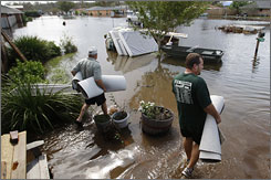 Ray Domangue, left, and Richard Sasser haul carpet Sunday from Sasser's flooded home near Chauvin, La.