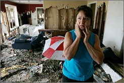 Korkie Smith looks at the devastation of her neighbor Renee Napier's house in the aftermath of Hurricane Ike in Baytown, Texas, Tuesday.