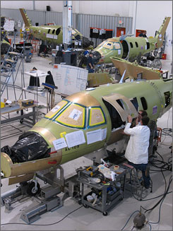 "Technicians work on the structure of a very light jet manufactured at the Eclipse Aviation facility in Albuquerque, N.M. in Dec. 2007. A House transportation committee investigation found a ""reduced level of vigilance on the FAA's part"" when approving the jet's design, according to a report."