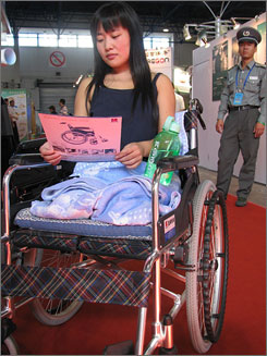 Chen Wen, 23, examines wheelchair models at a Beijing exhibition, 12 September 2008. The tourism graduate from a village near Baoding in Hebei province, lost her legs in a traffic accident this July. Her family has exhausted its savings in hospital fees, and lacks the money to pay for prosthetic limbs.