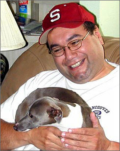 Metrolink engineer Robert Sanchez holds one of Lilian Barber's Italian greyhounds. Sanchez, 46, died in the commuter locomotive that slammed head-on into a freight in Los Angeles Friday, killing 25 passengers and injuring nearly 140.