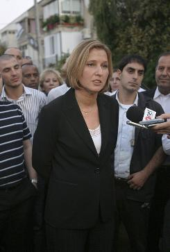 Israel's Foreign Minister Tzipi Livni, center, speaks to the media outside her home in Tel Aviv. Livni was narrowly elected leader of Israel's ruling party and vowed to start work immediately on forming a new coalition that will let her succeed the scandal-hit Ehud Olmert as prime minister.