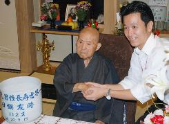 Tomoji Tanabe, left, the world's oldest man is congratulated by Miyakonojo Mayor Makoto Nagamine on his 113th birthday  at his home in Miyakonojo on Japan's southern island of Kyushu.