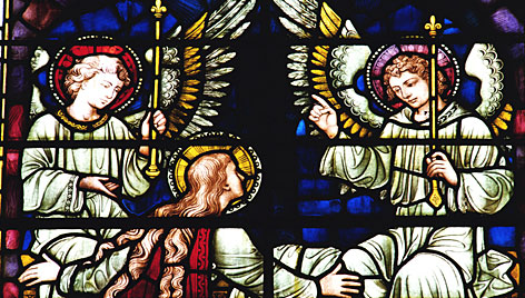 Angels depicted in a church's stained glass windows. The majority of Americans believe a guardian angel has kept them safe.