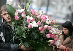A young man in Moscow carries flowers on Valentine's Day in 2007. Valentine's Day and Halloween are growing popular in Russia.