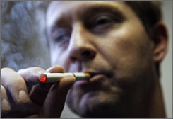 "A Dutch man smokes a ""supersmoker,"" an electronic device that contains cartridges with different concentrations of nicotine. The Netherlands does not include these devices in its public smoking ban."