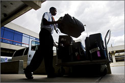 Baggage handler Mikaaill Heard loads luggage onto a cart outside the American Airlines terminal at Philadelphia International Airport in Philadelphia. With their slow travel season now upon them, airlines face the dual challenges of increasing revenue to cover heavy fuel costs while also improving their product to give air travelers a return on their extra investment.