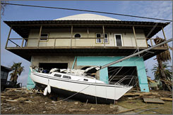 A battered boat rests in the yard of a home in the aftermath of Hurricane Ike in Galveston, Texas.