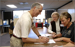 Gerry Biasiolli signs up to vote at the Urban Government Center Thursday in Louisville, Ky, while poll workers Sally Williamson, right, and Christine Blankenship watch. Residents of Virginia, Kentucky and Georgia are among the first in the nation eligible to vote in person, as well as by mail.