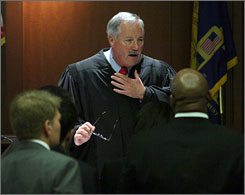 Judge James Bodiford, center, calls prosecutor Clint Rucker, right, and defense team member Robert McGlasson to the bench during opening arguments at the Atlanta Municipal Court site on Monday.