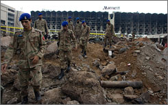 Pakistan army officials on Sunday walk through the rubble left from Saturday's truck bombing at the Marriott hotel in Islamabad, Pakistan.