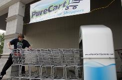 Potter's Piggly Wiggly stocker Cory Smith, 19, of South Milwaukee, pushes shopping carts through a PureCart disinfecting machine outside the store in Oak Creek, Wis.