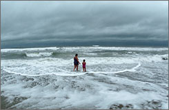 Alissa Allman, left, and her daughter, Kyla, 7, both of Rock Hill, S.C., venture into the sea at Wrightsville Beach, N.C., on Thursday. The storm came ashore overnight in the Carolinas, bringing rain and wind.