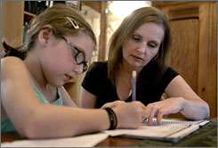 Lori Peterson helps her daughter Isabella, 9, with homework Wednesday, Sept. 17, 2008, in St. Louis. After living in St. Louis for more than a decade, the Petersons are fed up with a public school district that has been in disarray for years and are moving to the suburbs. Lori Peterson blames frequent turnover in the superintendent's job for adding to the school turmoil.