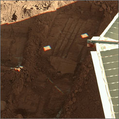 The edge of a solar panel on NASA's Phoenix Mars Lander, right, is seen in a trench on the surface of Mars, where a sample of soil was taken by the lander. NASA announced Monday that the spacecraft discovered two minerals in the Martian soil that suggest interaction with water in the past.
