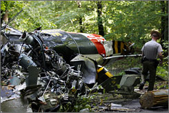 A police officer walks through the wreckage of a medical helicopter that crashed and killed four people Saturday night in Maryland.