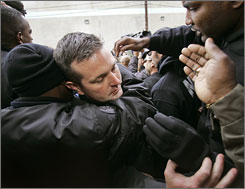 Sgt. Robert Gisevius Jr., second from left, hugs a fellow officer as he and seven other New Orleans cops turned themselves in Jan. 2, 2007 in connection with deadly shootings post-Katrina.