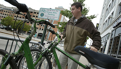 Andy Rosendahl restocks a Green Bike rack Monday in Green Bay, Wis. Some of the bike-sharing program's bikes were stolen, so the city will re-evaluate the program's honor system when the bikes are stored this winter.