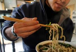 A man uses chopsticks to eat noodles. At Chinese restaurant buffets, only 9% of heavy patrons use chopsticks -- the rest use forks, according to a Cornell University study.